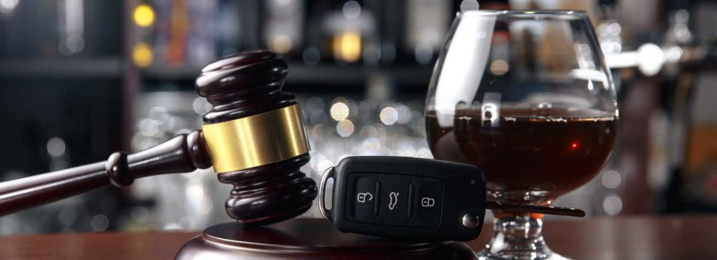 Picture of glass of alcohol next to car keys and gavel
